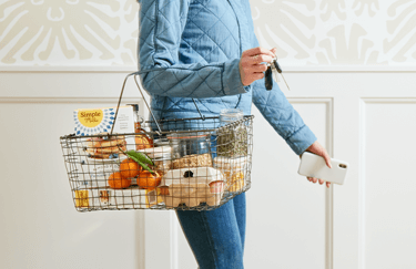 Woman holding a basket fillet with groceries including Simple Mills Almond Flour Baking Mixes