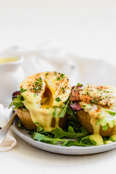 Eggs-Benedict,-savory,-top-angled-view,-off-white-background.jpg